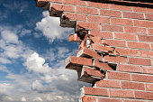 Broken brick wall and blue sky with clouds.