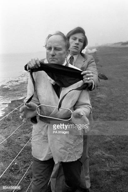 Escapologist Ron Cunningham is seen with his soon David who is blindfolding him on the cliffs near Brighton today When he had been hooded as well Ron...