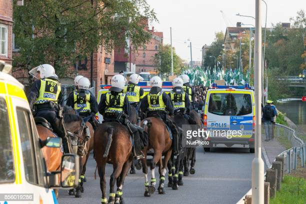 Escorted by a massive police contingent members of the Nordic Resistance Movement walk back to their cars after failing to complete their march...
