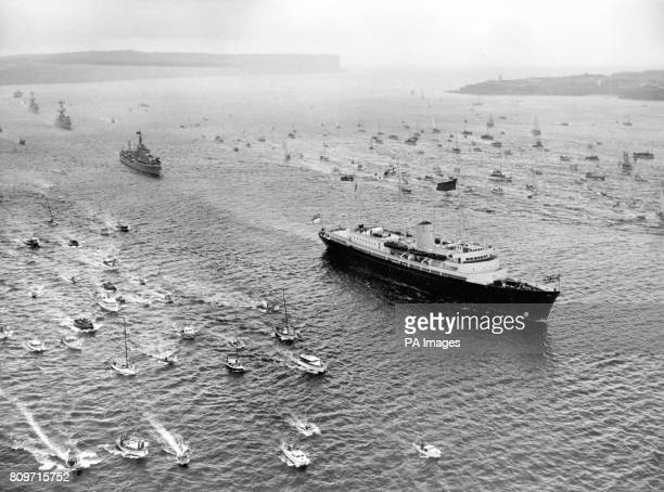 Escorted by an armada of small craft the Royal Yacht Britannia bearing Queen Elizabeth II and the Duke of Edinburgh arrives off Sydney Heads Three...