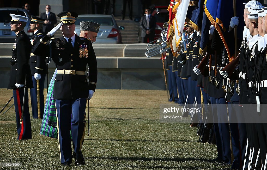 Escorted by Commander of Troops Col. James Markert (L), Afghan President <a gi-track='captionPersonalityLinkClicked' href=/galleries/search?phrase=Hamid+Karzai&family=editorial&specificpeople=121540 ng-click='$event.stopPropagation()'>Hamid Karzai</a> (2nd L) bows as he reviews the honor guards during a full military honors ceremony welcoming Karzai to the Pentagon January 10, 2013 in Arlington, Virginia. Karzai is on a visit in Washington, including a meeting with U.S. President Barack Obama at the White House, to discuss the continued transition in Afghanistan and the partnership between the two nations.