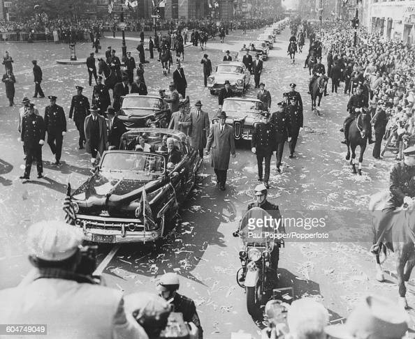 Escorted by policemen on foot horseback and on motorcycles Queen Elizabeth II rides in a bubble top Lincoln limousine car as part of a royal...
