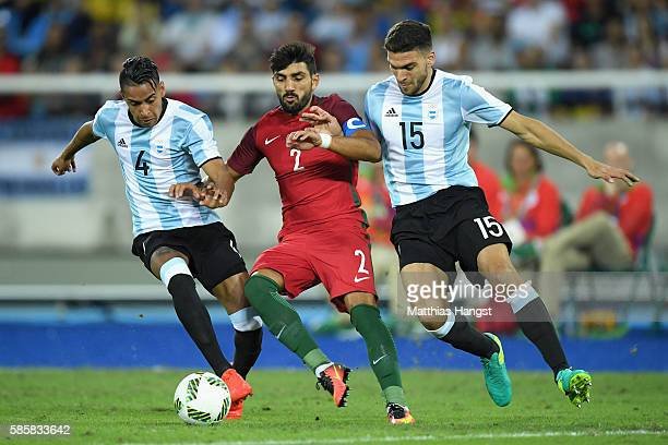 Esgaio Ricardo of Portugal battles for the ball against Jose Luis Gomez and Lisandro Magallan of Argentina during the Men's Group D first round match...