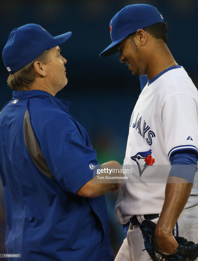 Esmil Rogers #32 of the Toronto Blue Jays reacts after being relieved by manager <a gi-track='captionPersonalityLinkClicked' href=/galleries/search?phrase=John+Gibbons&family=editorial&specificpeople=218120 ng-click='$event.stopPropagation()'>John Gibbons</a> #5 in the seventh inning during MLB game action against the Colorado Rockies on June 18, 2013 at Rogers Centre in Toronto, Ontario, Canada.