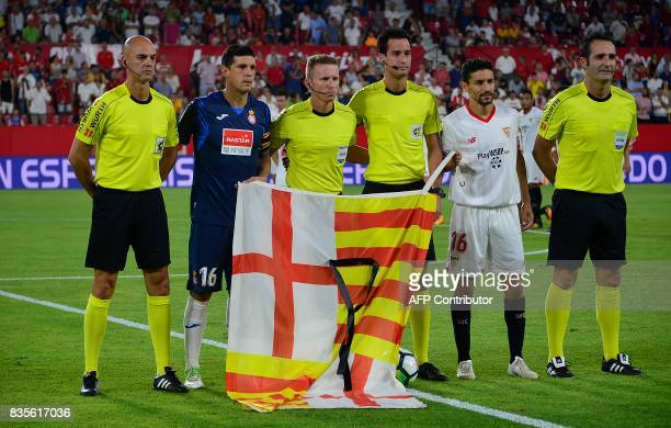 Espanyol's defender Javier Lopez Sevilla's midfielder Jesus Navas and referees pose with the flag of Barcelona and a black ribbon in tribute to the...