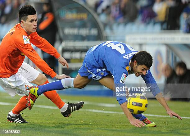 Espanyol's forward Jose Maria Callejon vies with Getafe's defender Miguel Torres during the Spanish league football match Getafe CF vs RCD Espanyol...