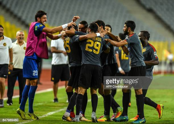 Esperance of Tunis' players celebrate after scoring a goal during the CAF Champions League quarterfinal firstleg football match between Egypt's...