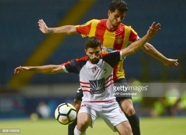 Esperance's Ali Machani fights for the ball with Fath Union Sport's Mohamed Fouzair during the Arab Club championship semifinal match Tunisian Tunis...