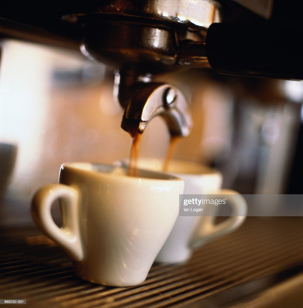 Espresso being poured into cups from machine in cafe, close-up : Stock Photo