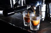 Professional espresso machine brewing a coffee. Coffee pouring into shot glasses