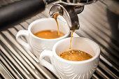 Espresso machine pouring coffee in white cups