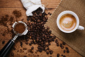 Espresso coffee overhead with spout and coffee beans on a wooden table
