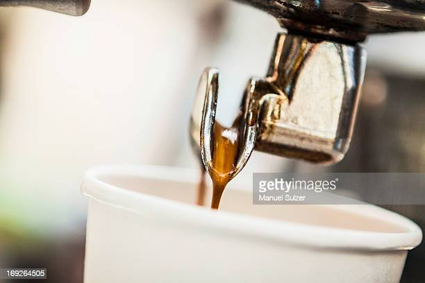 Espresso pouring from machine into cup