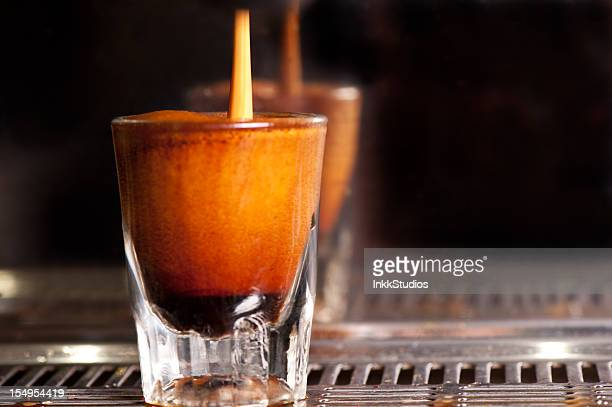 Espresso pouring into a shot glass on the coffee machine.