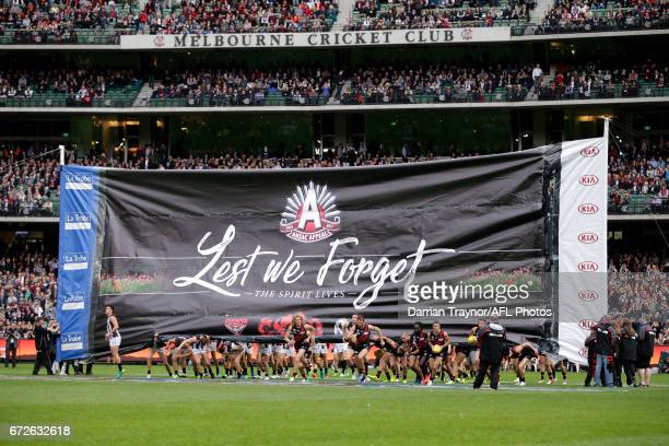 Essendon and Collingwood players run through a joint banner before the round five AFL match between the Essendon Bombers and the Collingwood Magpies...