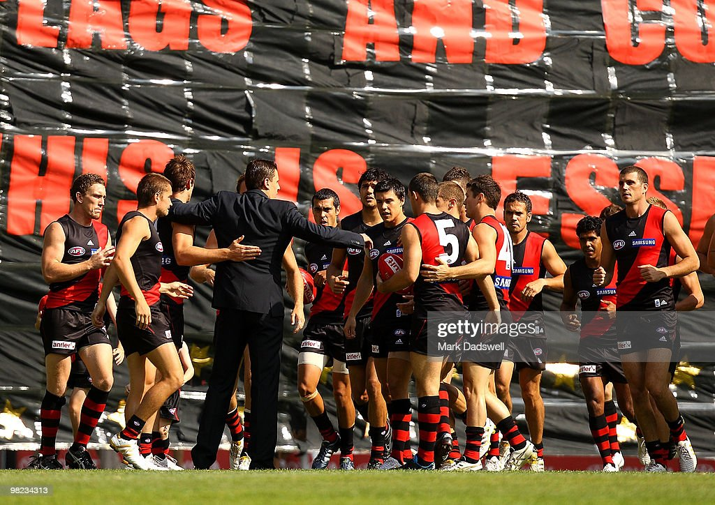 Essendon players run through the banner and are then addressed by former captain Matthew Lloyd during the round two AFL match between the Essendon...
