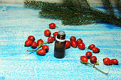 A bottle of rosehip seed oil on a wooden table, with fresh rosehips in the background