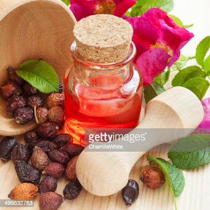 essential oil in glass bottle, dried rose-hip berries in wooden : Stock Photo