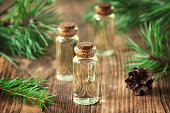 Essential oil of pine and spruce in small glass bottles on a wooden background. Soft focus.