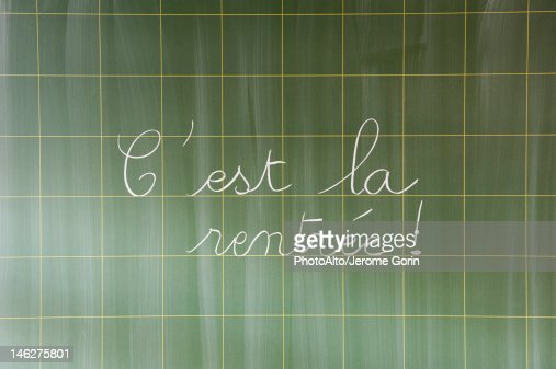 C'est la rentree' hand written in cursive on blackboard