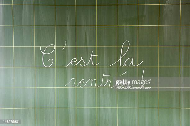 C'est la rentree' hand written in cursive on blackboard