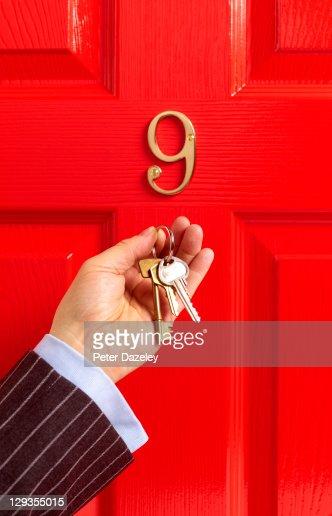 Estate agent and keys in front of red door