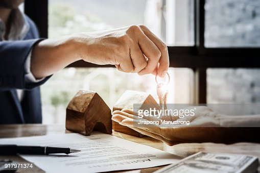 estate agent giving house keys  of customer  and holding dollar us bank at  agency office. agreement concept. : Stock Photo