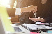 estate agent giving house keys to couple and sign agreement in office