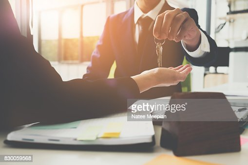 estate agent giving house keys to man and sign agreement in office : Stock Photo