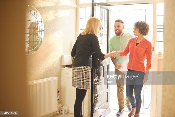 estate agent welcoming a couple to house viewing