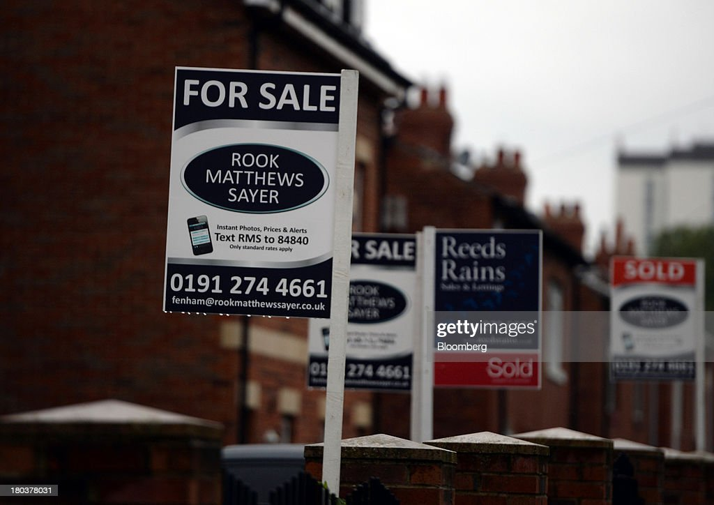 Estate agents' 'For Sale' and 'Sold' signs stand in the rain in front of a row of terraced residential houses in Newcastle-upon-Tyne, U.K., on Wednesday, Sept. 11, 2013. U.K. house prices rose for a seventh month in August and will probably continue to increase through the rest of the year, according to a report by Halifax. Photographer: Nigel Roddis/Bloomberg via Getty Images