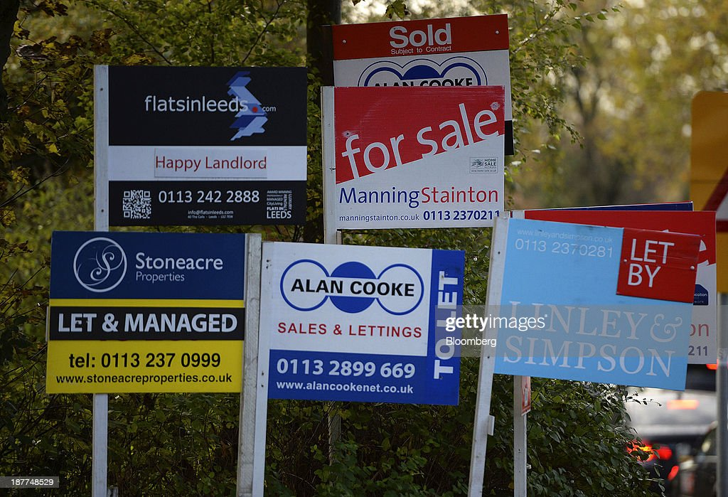 Estate agents 'for sale', 'to let' and 'let by' boards stand near residential buildings in Leeds, U.K., on Tuesday, Nov. 12, 2013. Under Bank of England Governor Mark Carney's forward-guidance policy, the central bank has pledged to not to withdraw stimulus at least until unemployment falls to 7 percent. Photographer: Nigel Roddis/Bloomberg via Getty Images