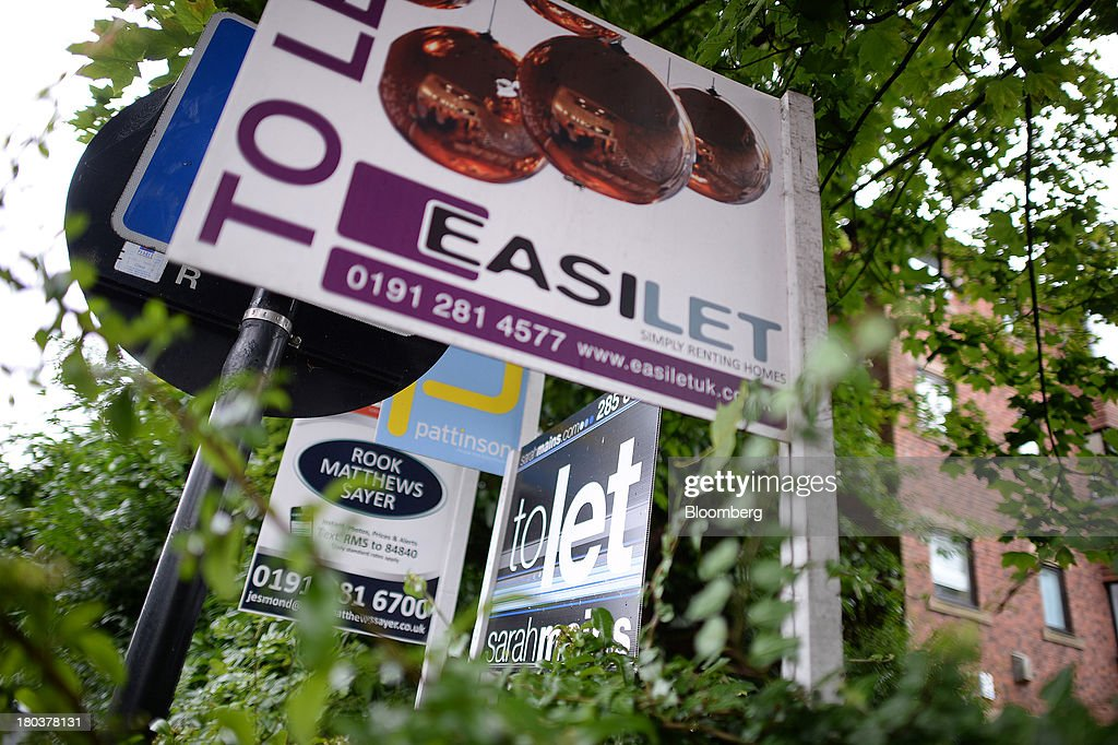 Estate agents' 'For Sale,' 'To Let' and 'Let By' signs stand outside residential property in Newcastle-upon-Tyne, U.K., on Wednesday, Sept. 11, 2013. U.K. house prices rose for a seventh month in August and will probably continue to increase through the rest of the year, according to a report by Halifax. Photographer: Nigel Roddis/Bloomberg via Getty Images