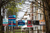 Estate agent's 'Sold' 'Let By' and 'For Sale' signs stand outside a residential apartment complex in the Clapham district of London UK on Thursday...