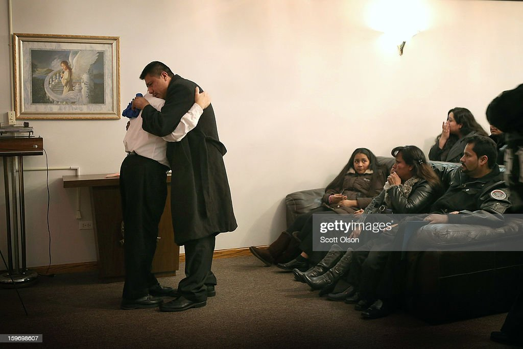 Esteban Dorantes (R), the father of Rey Dorantes, embraces Decon Antonio Navarro following a prayer at his son's wake on January 17, 2013 in Chicago, Illinois. Fourteen-year-old Rey Dorantes died after being shot 6 times while he was sitting on the front porch of his home while talking on the phone on January 11. Dorantes' murder was the 21st homicide recorded in Chicago for 2013, a city which saw more than 500 homicides in 2012.
