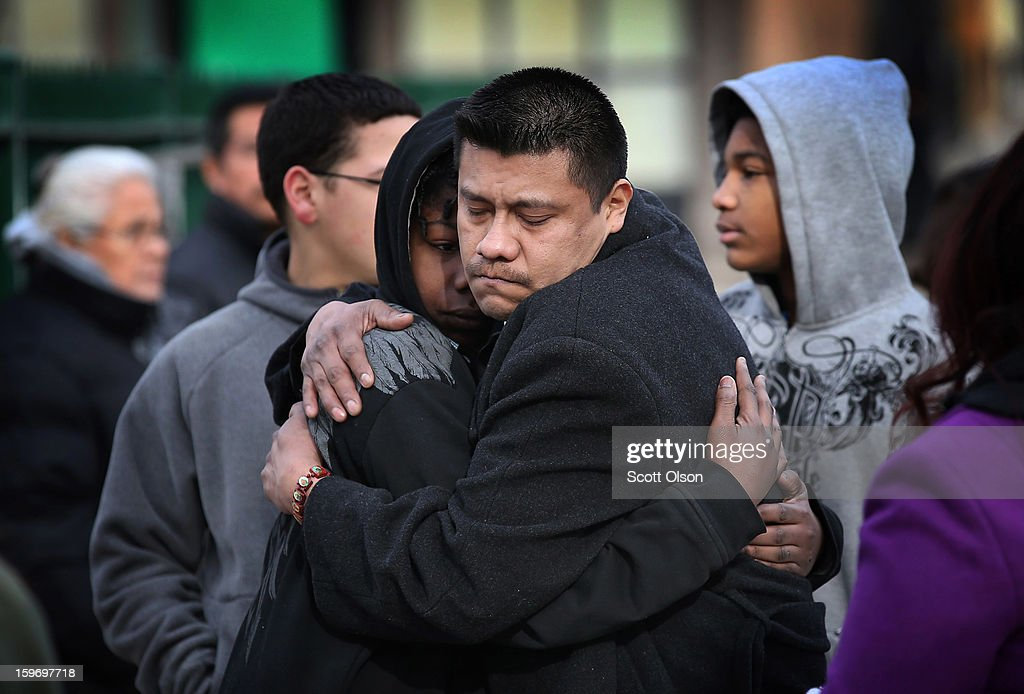 Esteban Dorantes (R), the father of Rey Dorantes, gets a hug from one of his son's friends, Clinton Salisbury, following a funeral mass at St. Mark Church on January 18, 2013 in Chicago, Illinois. Rey Dorantes, 14, died after being shot six times while he was sitting on his front porch talking on the phone on January 11. Dorantes's murder was the 21st homicide recorded in Chicago for 2013, a city which saw more than 500 homicides in 2012.