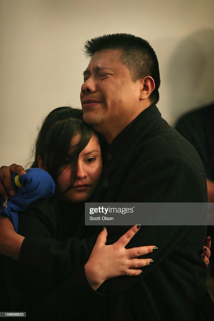 Esteban Dorantes (R), the father of Rey Dorantes, is comforted at his son's wake on January 17, 2013 in Chicago, Illinois. Fourteen-year-old Rey Dorantes died after being shot 6 times while he was sitting on the front porch of his home while talking on the phone on January 11. Dorantes' murder was the 21st homicide recorded in Chicago for 2013, a city which saw more than 500 homicides in 2012.
