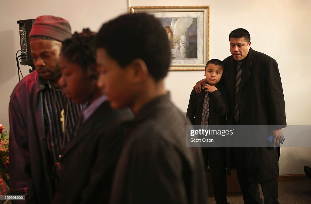 Esteban Dorantes, the father of Rey Dorantes, watches with his son Jesus as mourners view Rey's remains during a wake on January 17, 2013 in Chicago, Illinois. Fourteen-year-old Rey Dorantes died after being shot 6 times while he was sitting on the front porch of his home while talking on the phone on January 11. Dorantes' murder was the 21st homicide recorded in Chicago for 2013, a city which saw more than 500 homicides in 2012.