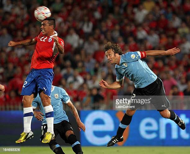 Esteban Paredes of Chile fights for the ball with Diego Lugano of Uruguay during a match between Chile and Uruguay as part of the 12th round of the...