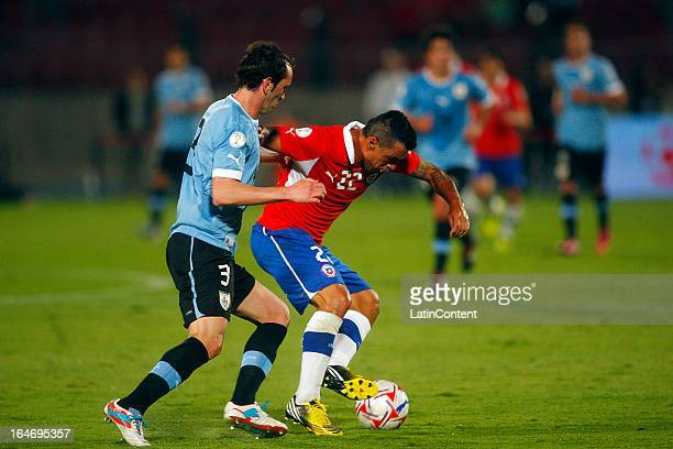 Esteban Paredes of Chile struggles for the ball with Diego Godin of Uruguay during a match between Chile and Uruguay as part of the 12th round of the...