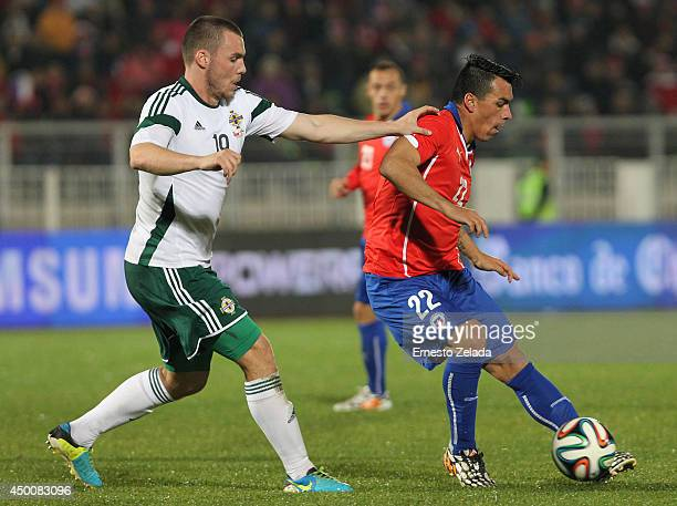 Esteban Paredes of Chile vies for the ball with Luke McCullough of Northern Ireland during the international friendly match between Chile and...