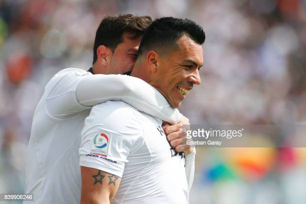 Esteban Paredes of ColoColo celebrates with teammate after scoring the third goal of his team during a match between ColoColo and U de Chile as part...