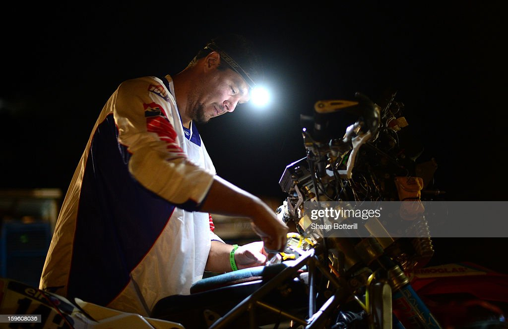Esteban Smith of Vamos Chile Rally Team works on his bike after completing stage 11 from La Rioja to Fiambala during the 2013 Dakar Rally on January 16 in Fiambala, Argentina.