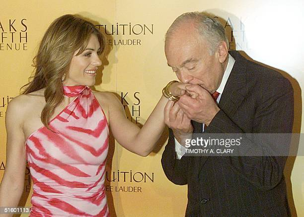 Estee Lauder spokesperson actress and model Elizabeth Hurley has her hand kissed by Estee Lauder Chairman Leonard Lauder as she arrives for a press...