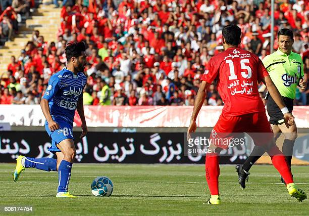 Esteghlal's Farshid Esmaeili is marked by Persepolis's Mohammad Ansari during their Persian Gulf Pro League derby football match between Persepolis...