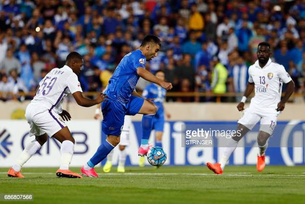 Esteghlal's Kaveh Rezaie kicks the ball past alAin's Saeed Juma during the 2017 AFC Champions League round 16 football match between Iran's Esteghlal...
