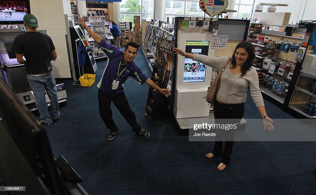 Estella Villar plays with Microsoft's new Kinect controller for the Xbox 360 as the Xbox representative Charles Leano (L) helps explains how to play to her at the Best Buy store on November 4, 2010 in Miami Beach, Florida. The Kinect went on sale today and uses sensors to read the players body language so controllers are not necessary to play Xbox games with the Kinect.