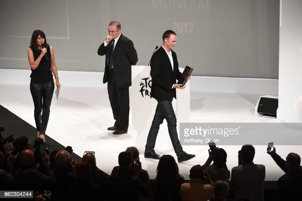 Estelle Denis and Bernard Hinault give the trophy to Christopher Froome during the presentation of the Tour de France 2018 at Palais des Congres on...