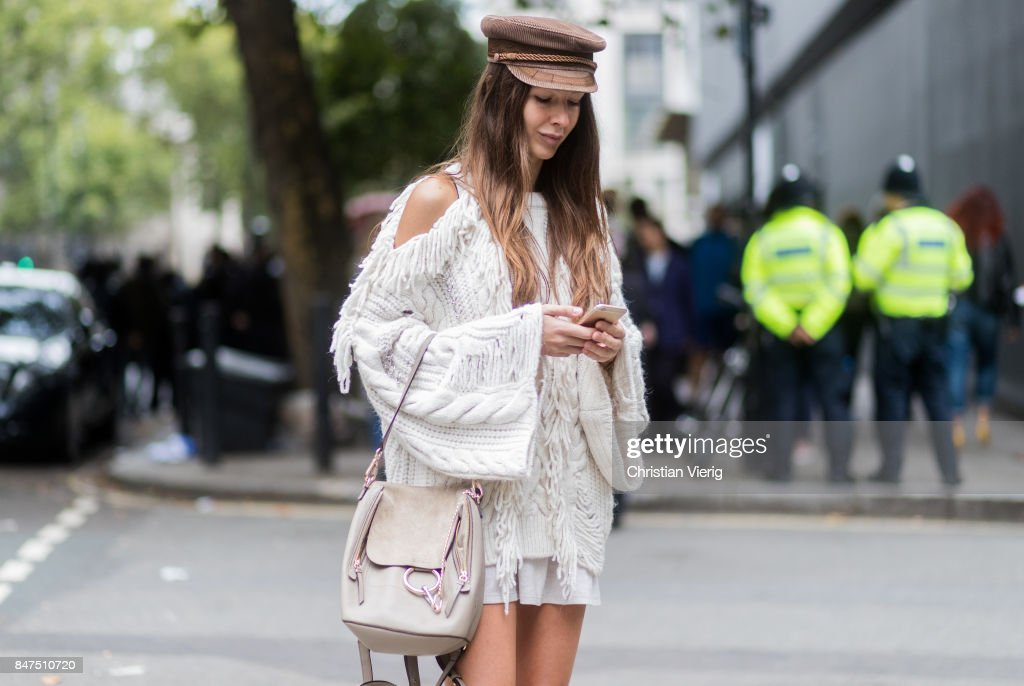Estelle Pigault writting a text message wearing a white knit, Chloe bag, slippers, socks, flat cap during London Fashion Week September 2017 outside Eudon Choi on September 15, 2017 in London, England.