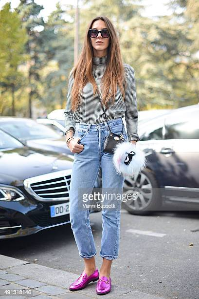 Esthelle Pigault poses wearing a vintage shirt Levis pants Fendi bag and Gucci loafers before the Celine show at the Tennis Club de Paris during...